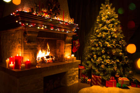 christmas tree ornaments: christmas tree with gifts near fireplace Stock Photo