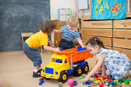 variance: two kids pull toy truck in kindergarten play room