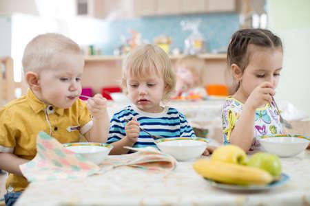 baby boys: kids group eating in kindergarten