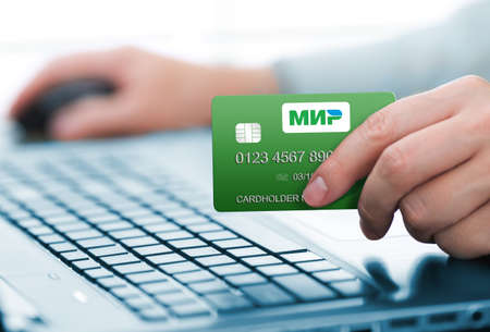 cvv: TOMSK, RUSSIA - JAN 19, 2017: Man holding MIR payment card. MIR is Russian national payment system.