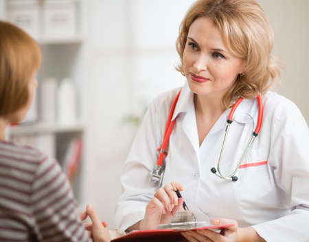 Doctor woman friendly communicating with patient in office