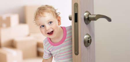 新しい部屋のドアの後ろに喜んでいる子供
