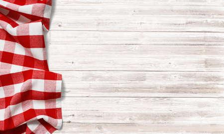 tovaglia di picnic checkered rosso su tavola di legno bianca