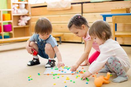 grupo de niños jugando juego de mosaico en el jardín de infantes