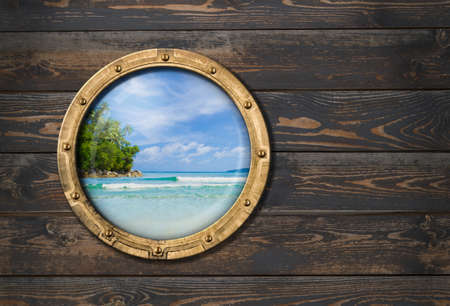 ship porthole on wooden wall with tropical island behind