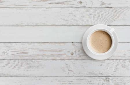 tasse à café sur la vue de dessus de table en bois blanc