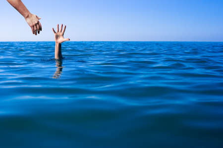 Help hand for drowning man life saving in sea water