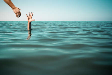 Help hand for drowning man life saving in sea or ocean.
