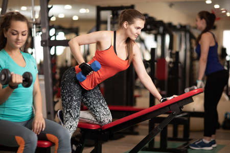 women having workout in gym with dumbbells