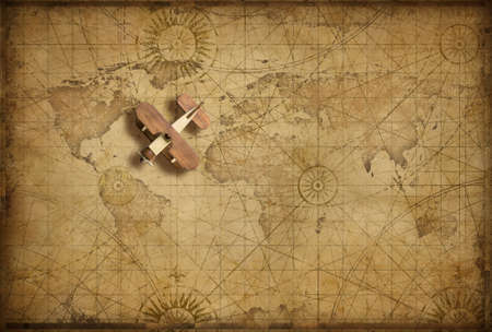 Small wood airplane over world nautical map as travel, explore and communication concept Standard-Bild