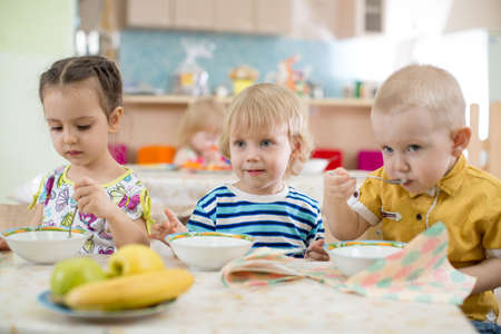 Kids eating in kindergarten or day care centre Standard-Bild - 119270202