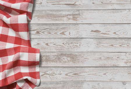mantel rojo doblado con mesa de madera blanca