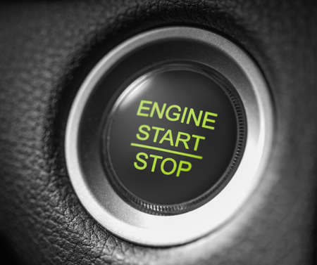 macro shot start stop engine car green button