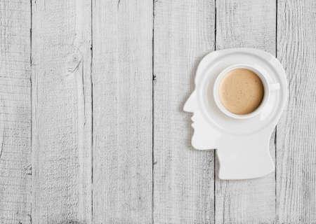 Taza de café en la placa en forma de cabeza humana