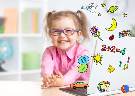Pleasured kid using notebook actively with great interest as multimedia encyclopedia and game center