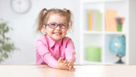 Happy kid girl in eyeglasses sitting at her table Imagens