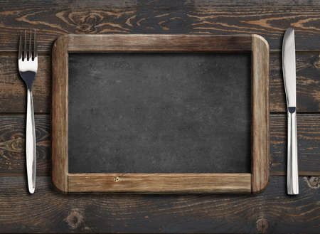 menu blackboard frame on old wooden dinning table with knife and fork Banco de Imagens