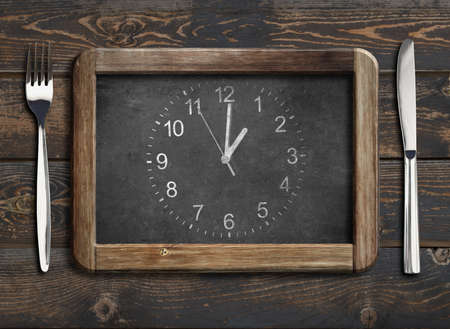 blackboard with clock face on old wooden dinning table with knife and fork