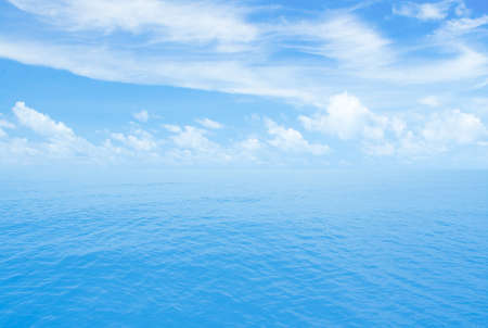 Ocean or seascape. Horizon line with partly cloud sky.