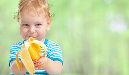 happy kid eating banana fruit Reklamní fotografie