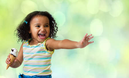 happy kid eating ice cream on green abstract background Imagens