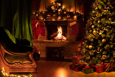 Christmas decorated tree in interior with fireplace, green armchair and curtains