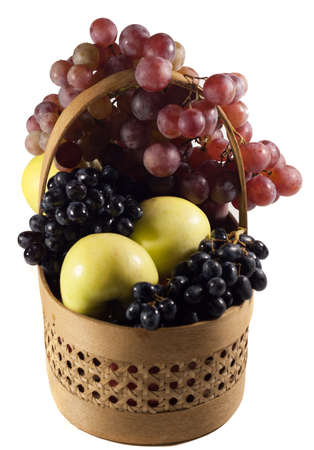 basket with white and red apples and grapes. Isolated photo