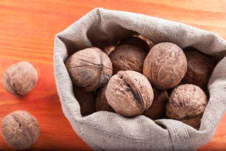 reg: The unshelled walnuts in the bag standing on the wooden background
