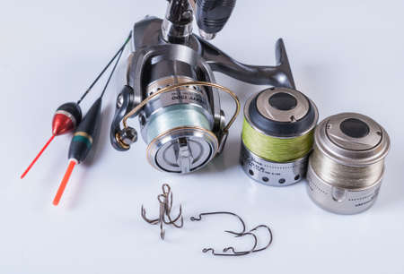 spinning reel: Fishing tackle - spinning reel, fishing line and hooks. On a white background, Not isolated Stock Photo