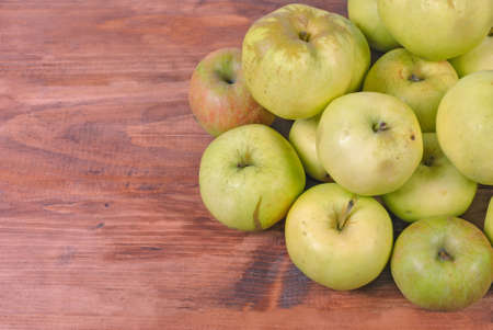 washed: a bunch of green apples on a wooden surface