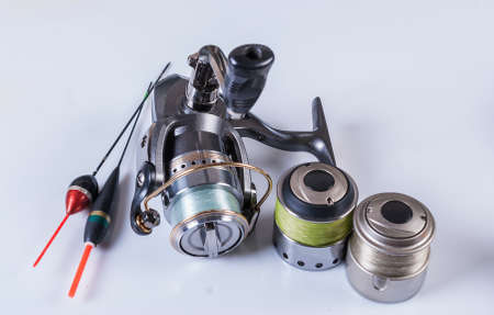 Fishing accessories reel, spools of fishing line, floats and a box of hooks Stock Photo