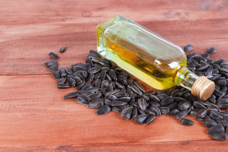 A small bottle of oil, sunflower and pumpkin seeds.