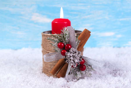 Hot red candle in a candlestick in the snow. With a place for placing an inscription