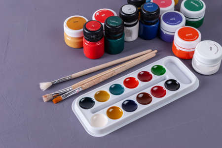 Colorful aquarelle paints in a box and brushes