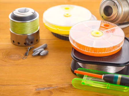 Three fishing tackles and a float, orange round boxes for baits and fishing line lying on wooden boards 免版税图像 - 108075241