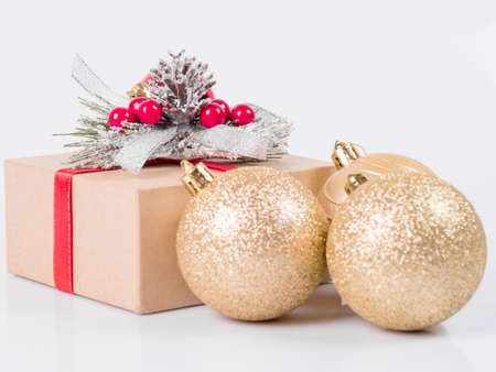 Christmas gift box decorated with a bow and red berries, two silvery Christmas balls on a white mirror background