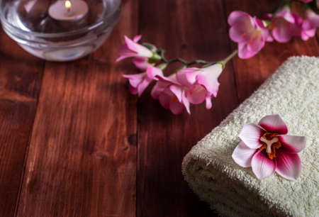 White towel with flowers and a burning candle on a wooden background. Selective focus Standard-Bild