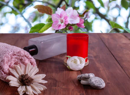 Red candle with white flowers, spa stones. Pink towel against the background of blooming flowers. Imagens