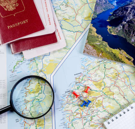 Map of Norway with a magnifying glass, passports and a guide for travel preparation