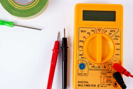 Yellow digital multimeter with a screwdriver on a white background Banco de Imagens - 132100258