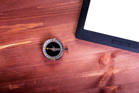 Compass and tablet with white screen on wooden background
