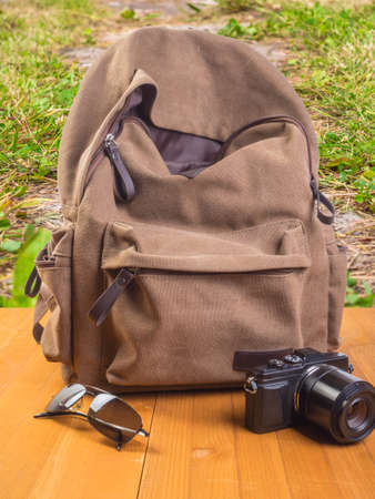 Backpack, camera and sunglasses on a wooden table