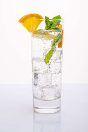A glass of mineral water decorated with a slice of orange and mint Stockfoto