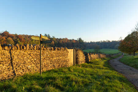 A path for a quiet autumn walk in the UK countryside with the evening sun on a stone wall
