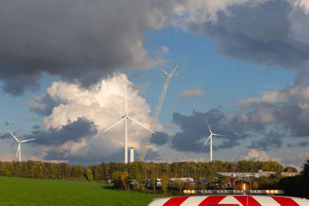 flashing lights of a working car and installation of new wind turbines and a beautiful cloudy sky in the background