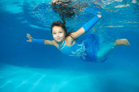 age 10 12 years: Girl presenting underwater fashion in pool