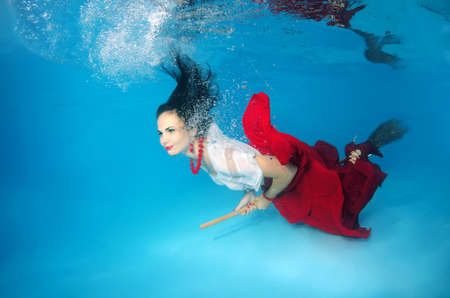 fair skinned: A young woman with big hair posing in a pool underwater