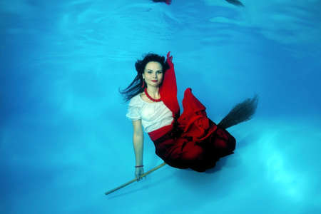 age 30 35 years: A young woman with big hair posing in a pool underwater