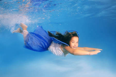 fair skinned: Girl presenting underwater fashion in pool