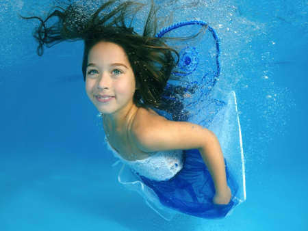 ten year old: Girl presenting underwater fashion in pool
